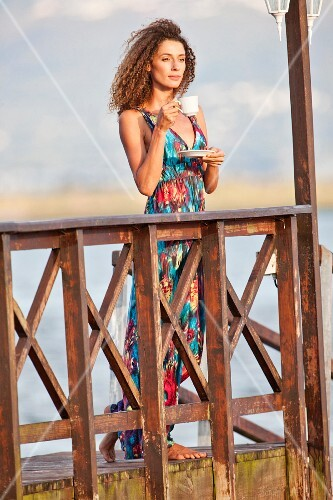 Young woman with cup of tea on jetty