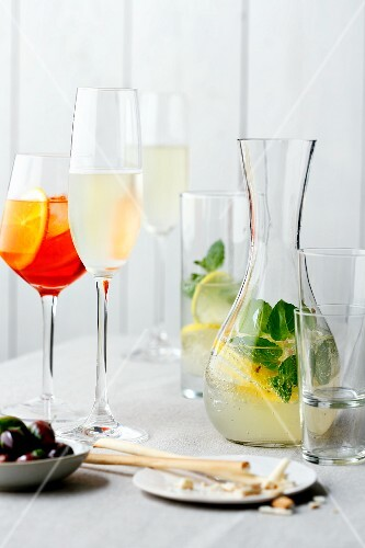 Various drinks in glasses and a caraffe