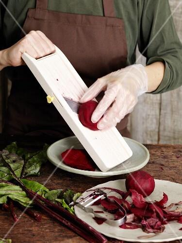 Beetroot being sliced with a vegetable slicer