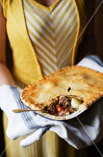A woman serving a sliced meat pie