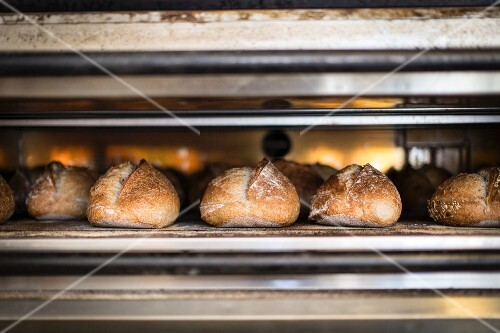 White bread being baked in an oven in a bakery