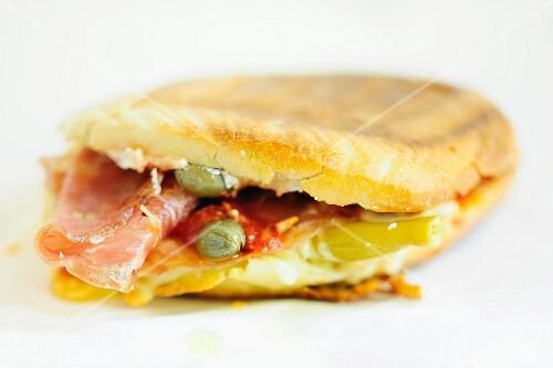 A ham, tomato and caper panini
