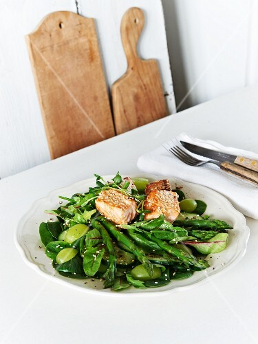 Sesame salmon on a bed of green vegetables