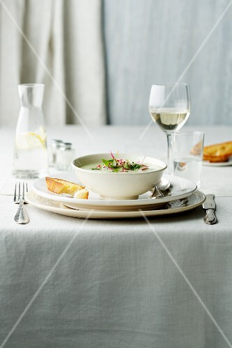 A table laid with creamy soup, water and wine