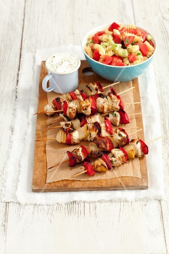 Chicken skewers with onions and pepper and a pasta salad with tomatoes and cucumber