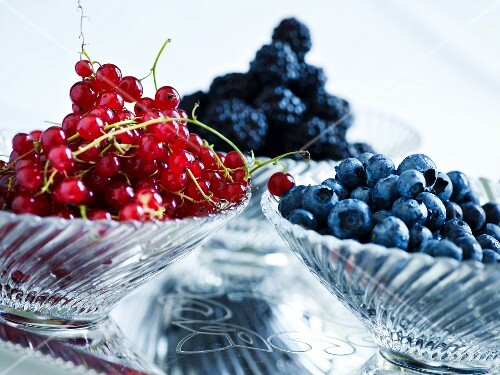 Redcurrants, blueberries and blackberries in glass bowls