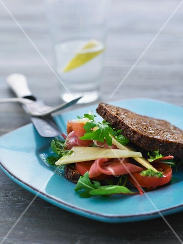 A rye bread sandwich with Parma ham, cheese, tomatoes and rocket