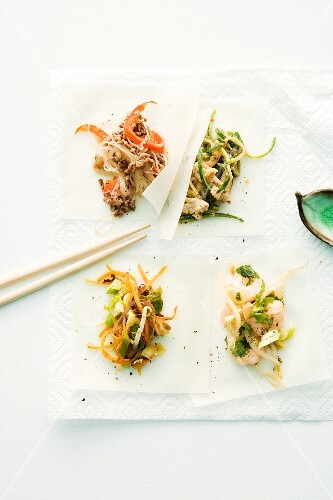 Four sheets of rice paper with various savoury fillings for spring rolls