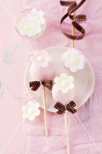 Birthday cake pops with sugared flowers and bows