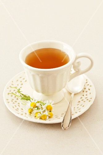 A cup of camomile tea and fresh camomile flowers
