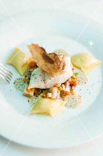 Zander fillet on a bed of vegetables with potato ravioli