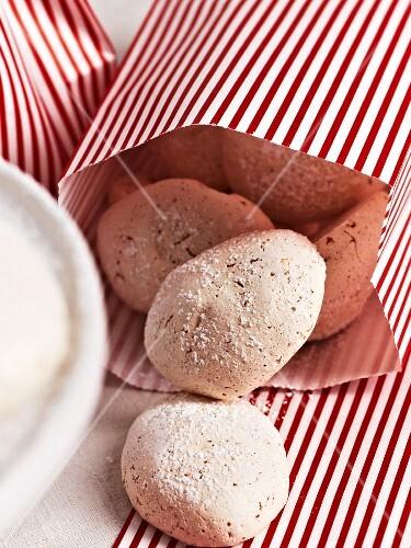 Vanilla meringues in a striped paper bag