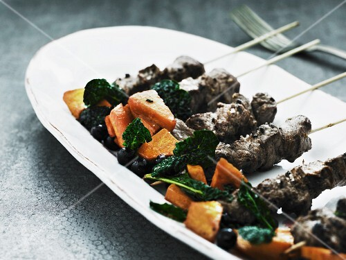 Game skewers with spinach and sweet potatoes