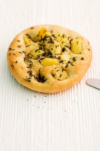 Focaccia with oregano potatoes on a wooden surface