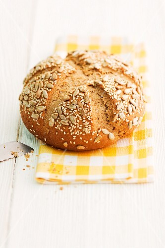 A loaf of sunflower seed bread on a checked napkin