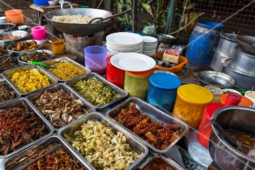 A fast food stand with various dishes in metal bowls at a market in Yangon