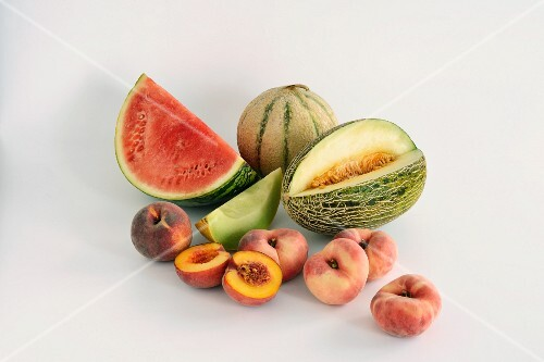 Various different melons and peaches against a white background