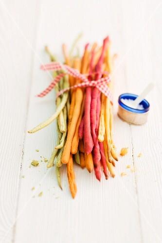 Various coloured breadsticks with salt