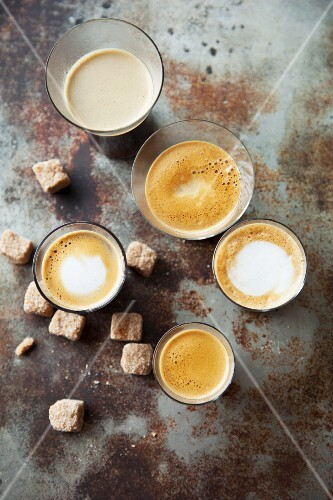 Various glasses of coffee with sugar cubes on a metal surface