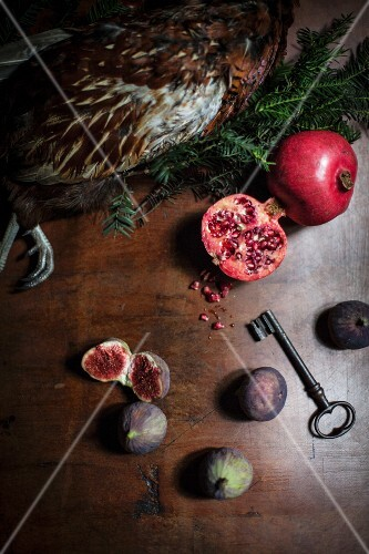 An arrangement featuring pheasant, pomegranates and figs