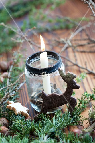 Christmas arrangement of candle in jam jar and reindeer-shaped biscuit