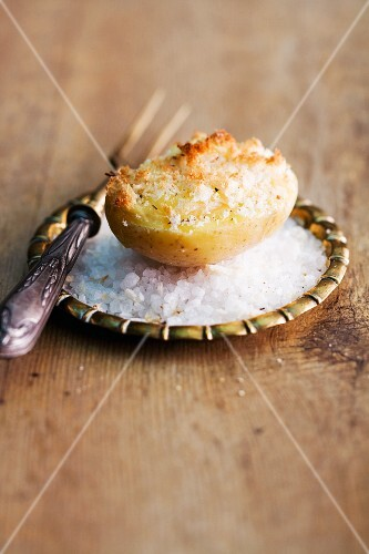 A gratinated baked potato on a bed of salt