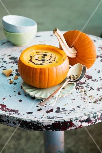 Pumpkin soup with pumpkin seeds served in a hollowed out pumpkin