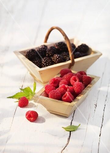 Raspberries and blackberries in wooden baskets