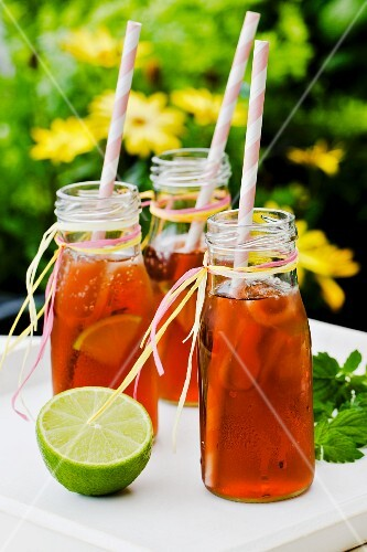 Three small bottles of iced tea with lime and peppermint on a tray