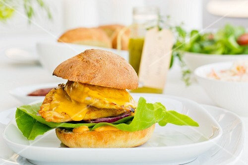 A chicken burger with mango sauce and red onions