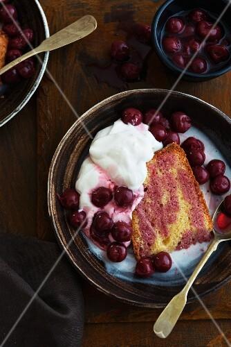 A slice of cherry cake with cream