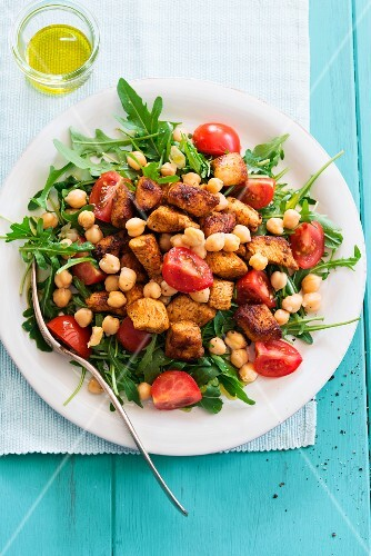 A rocket salad with chickpeas, tomatoes and pork