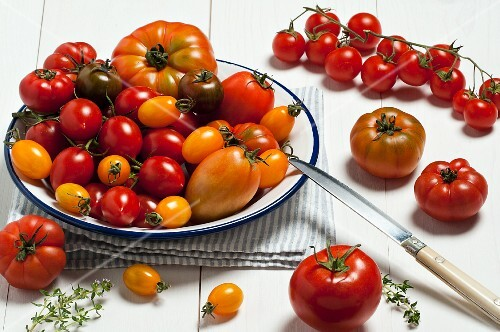 Various types of tomatoes on a plate and next to it