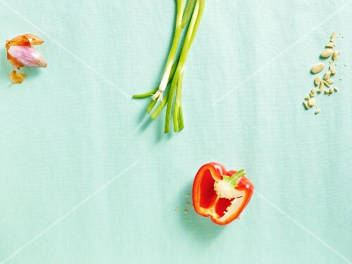 A shallot, spring onions and a pepper on a blue surface