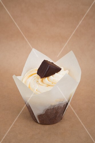 A chocolate cupcake decorated with orange cream and a chocolate-covered marzipan sweet