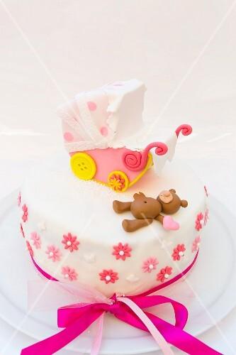 A lemon cake decorated with a pram and a teddy bear
