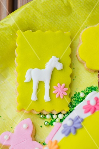 Shortcrust biscuits decorated with green fondant icing, flowers and a horse