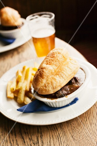 Steak and ale pie served with chips and a glass of ale