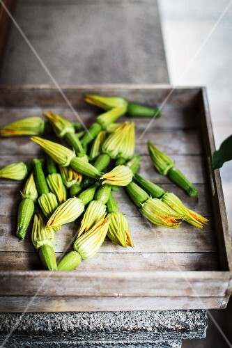 Baby courgettes with flowers on a wooden tray