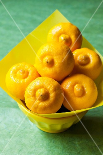 Bergamot lemons in a bowl lined with yellow paper