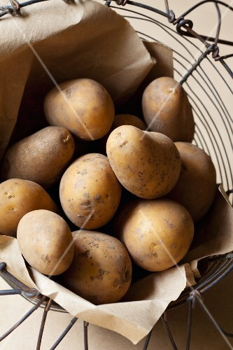 Potatoes in a wire basket lined with paper