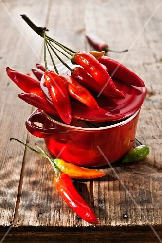 Chilli peppers in a red hot or wooden table