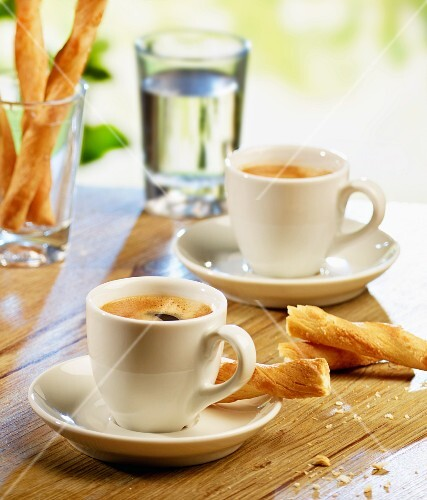 Two espressos, savoury breadsticks and a glass of water on a garden table
