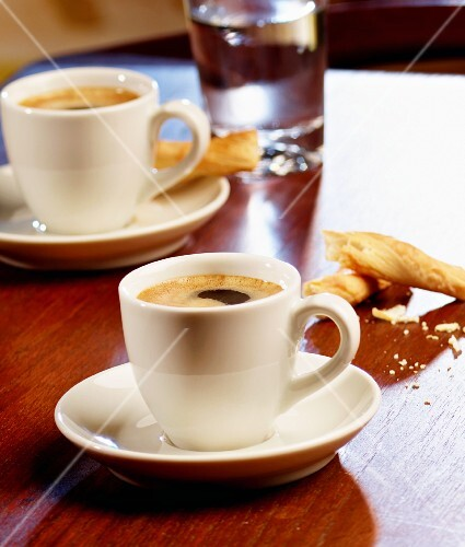 Three espressos, salted breadsticks and coffee beans on a table