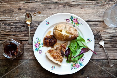A slice of onion tart with baked potato, salad and apple and courgette chutney