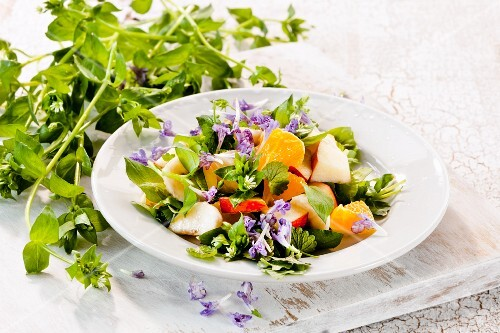 Fruit salad with chickweed and edible flowers