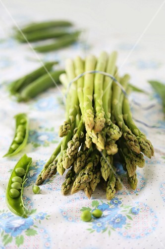 A bunch of green asparagus surrounded by peapods