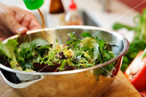 A fresh garden salad being drizzled with soy sauce