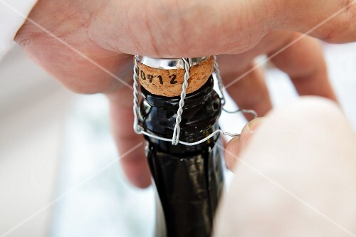 Hands opening a bottle of champagne