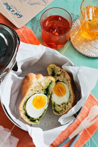 A bread roll filled with egg and spinach in a bread basket